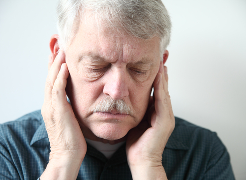 Man with TMJ holding jaw