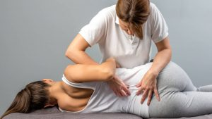 Young woman spinal manipulation by chiropractor
